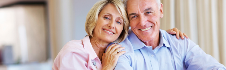 a mature couple smiling with white dental implants